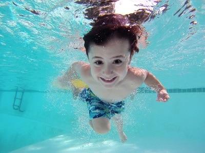 Enfant nageant sous l'eau dans une piscine